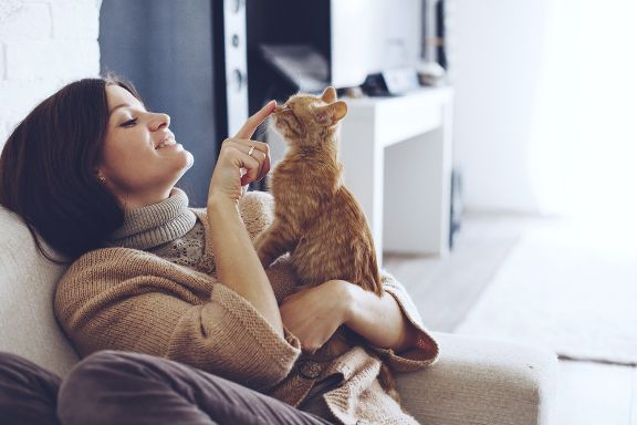 Woman holding orange kitten touching its nose